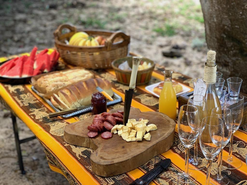 mesa de piquenique com frios, pães, frutas e bebidas