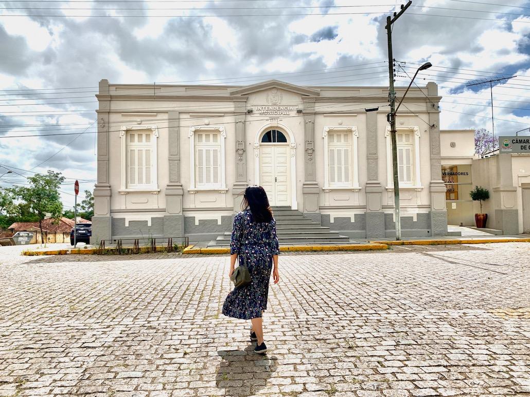 mulher em frente a prédio histórico em camaquã