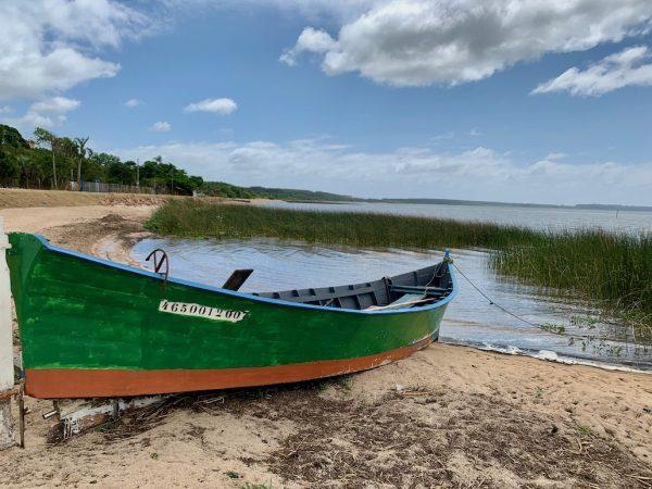 barco na areia em frente à lagoa