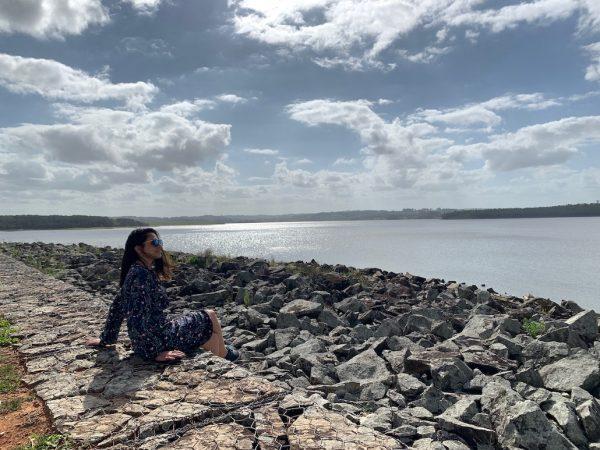 mulher em frente a lagoa cercada por pedras