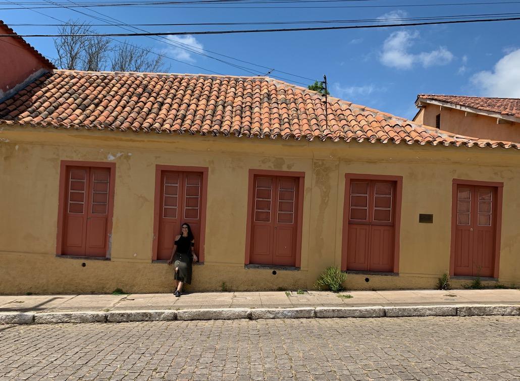 mulher em frente a casa de garibaldi em piratini
