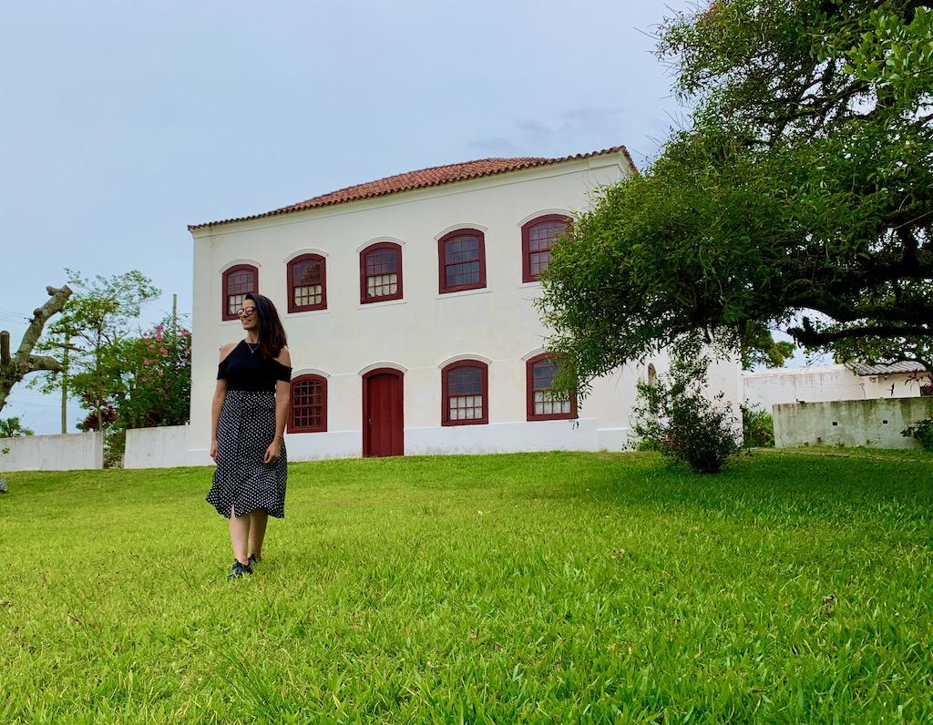 mulher em frente a casarão na fazenda do sobrado