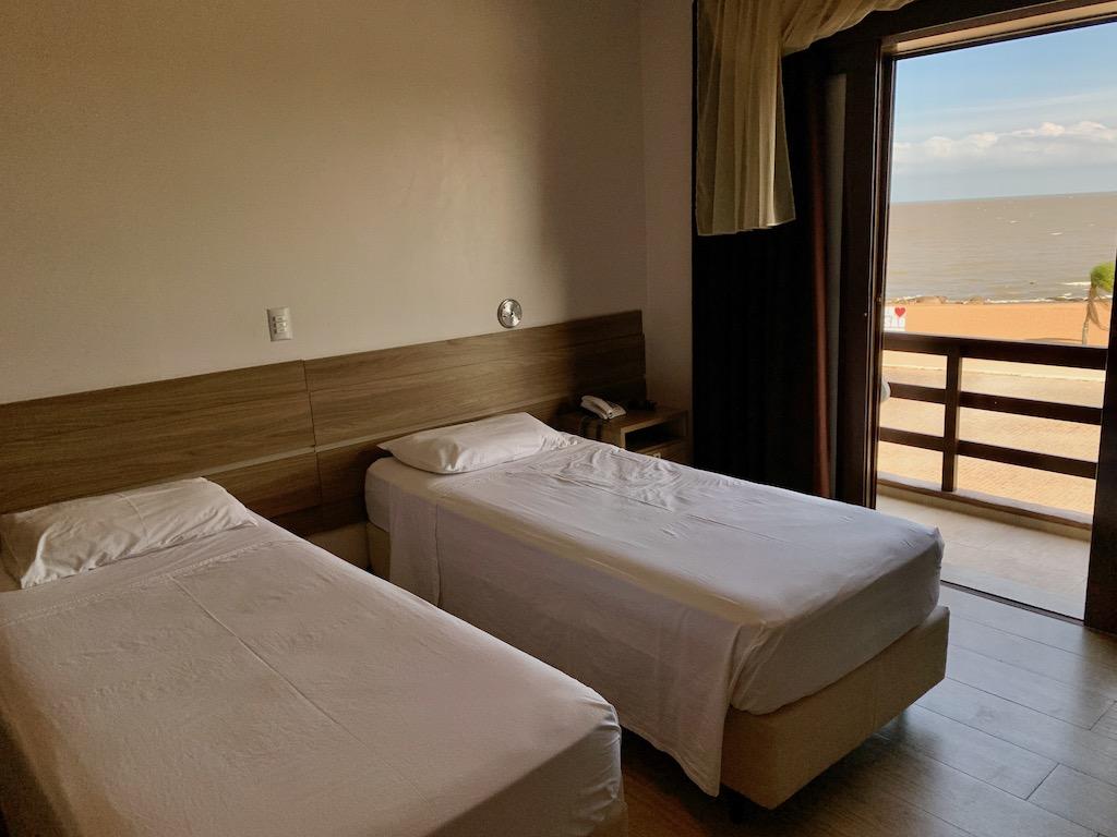 camas de solteiro em quarto de hotel com vista para a lagoa
