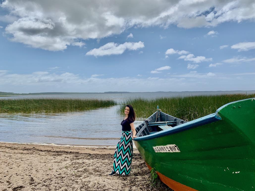 mulher em frente a barco na praia do jacarezinho