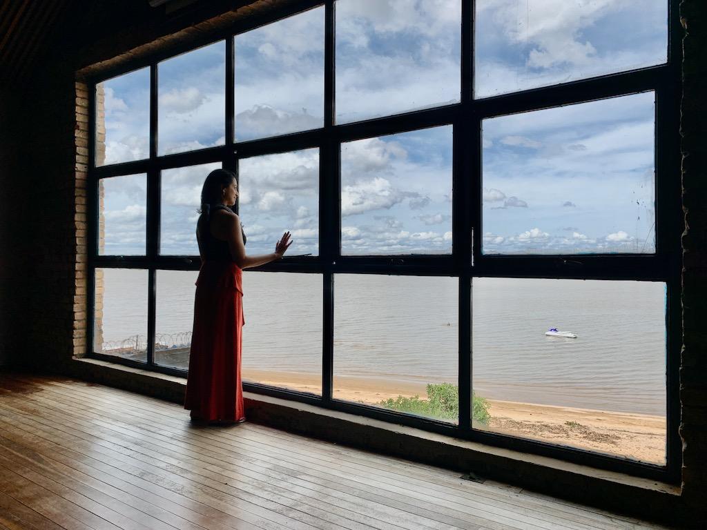mulher parada em frente a janela com vista para rio