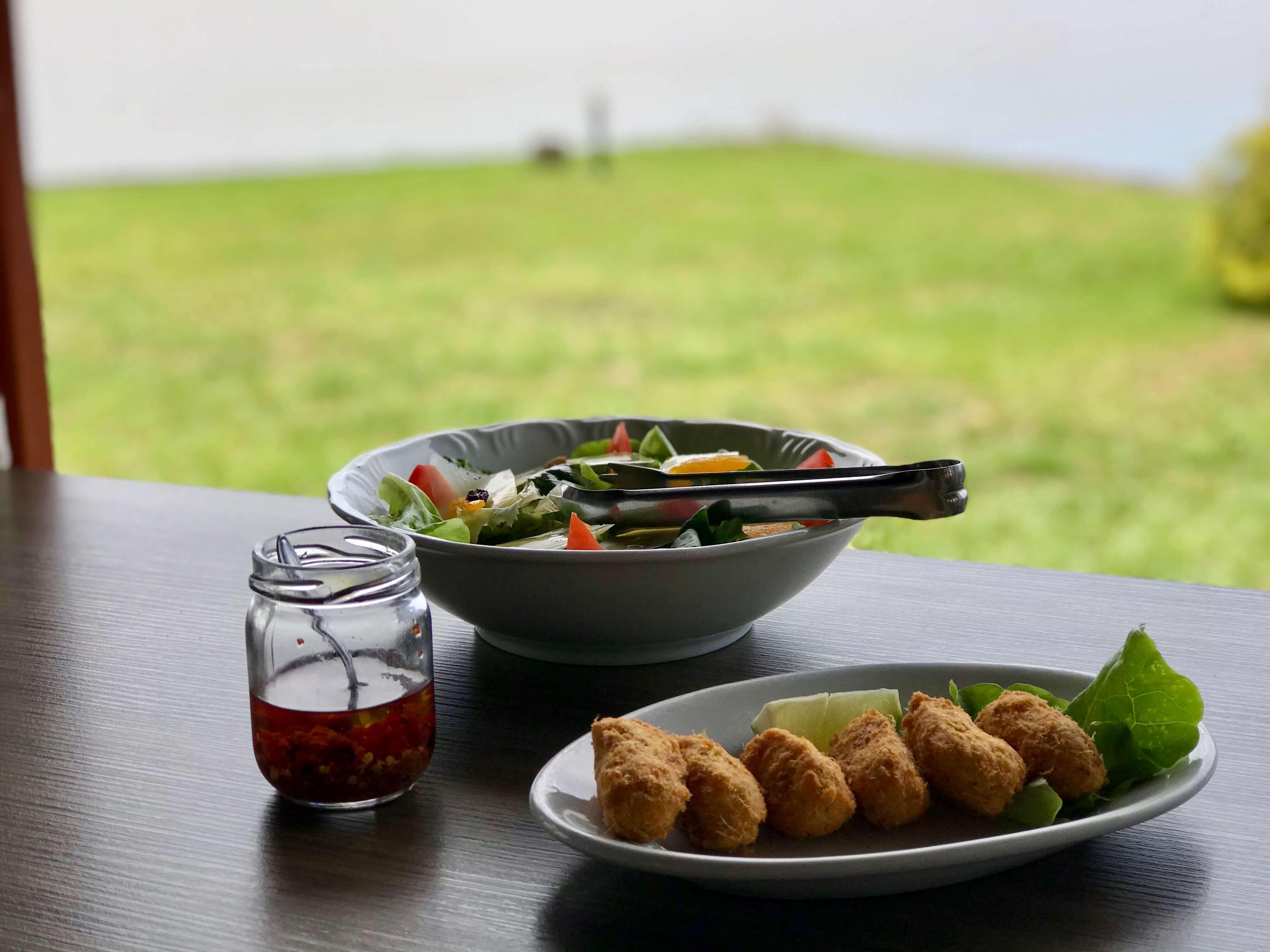 bolinho de bacalhau, salada e pote de pimenta