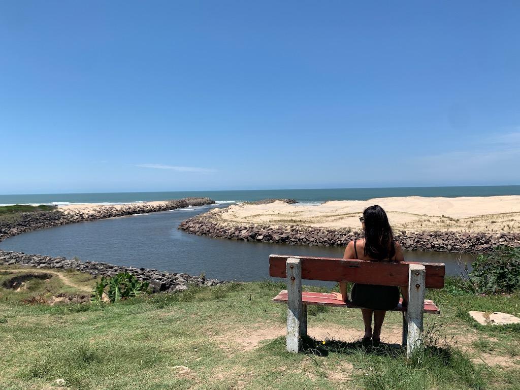 Arroio Chuí, um banco, uma pessoa, pedras e areia