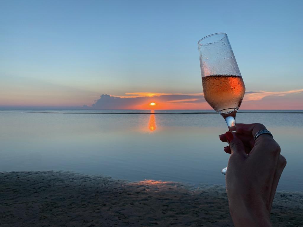 vista do pôr do sol com mão segurando taça de espumante