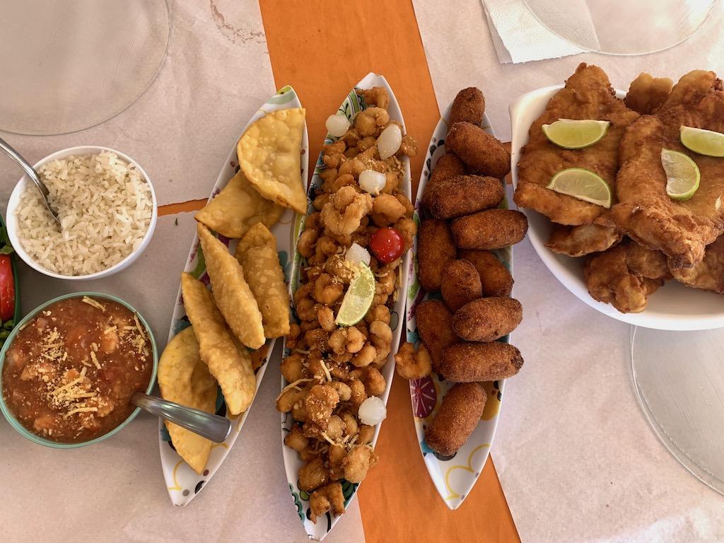mesa com petiscos de peixe fritos