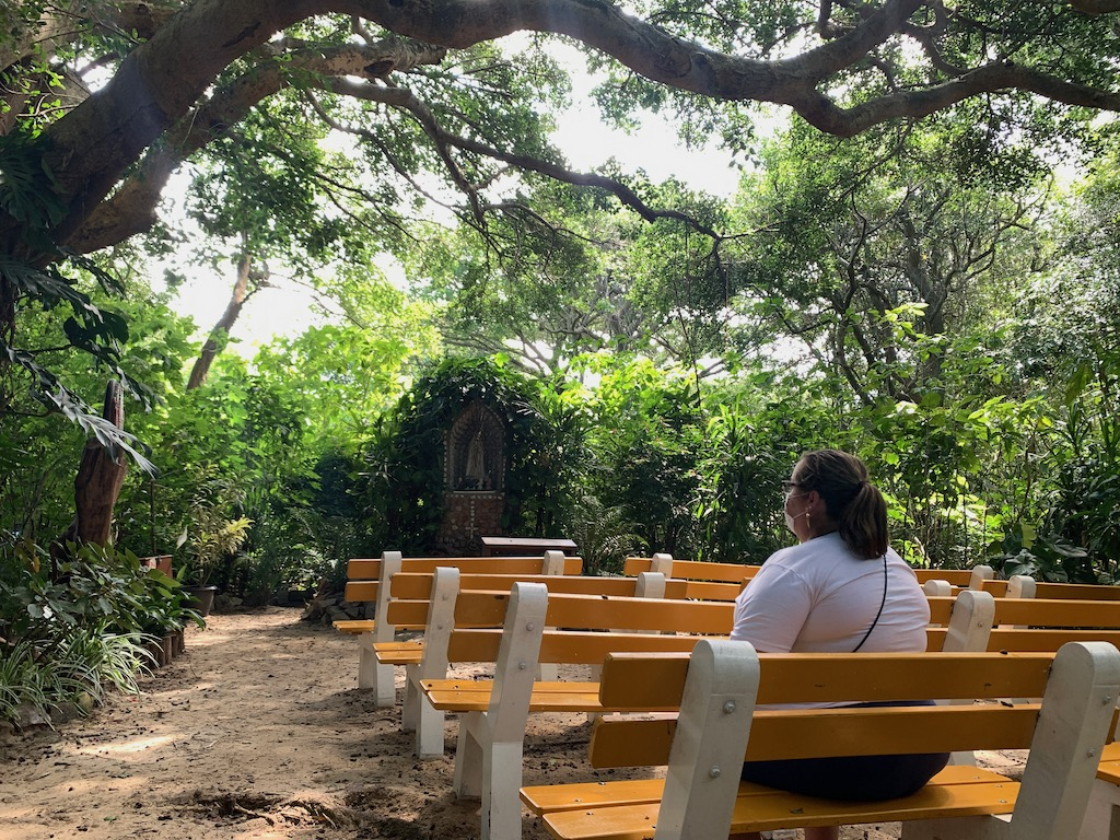 mulher sentada em banco de madeira na gruta