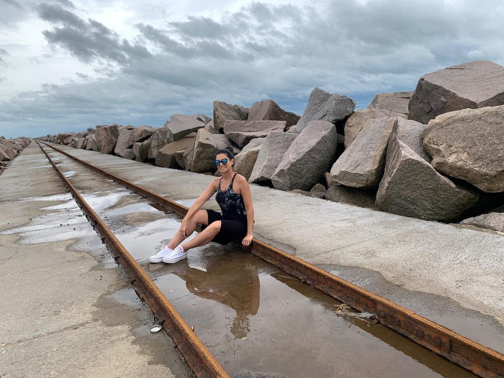 mulher sentada em molhes de rio grande em frente à lagoa