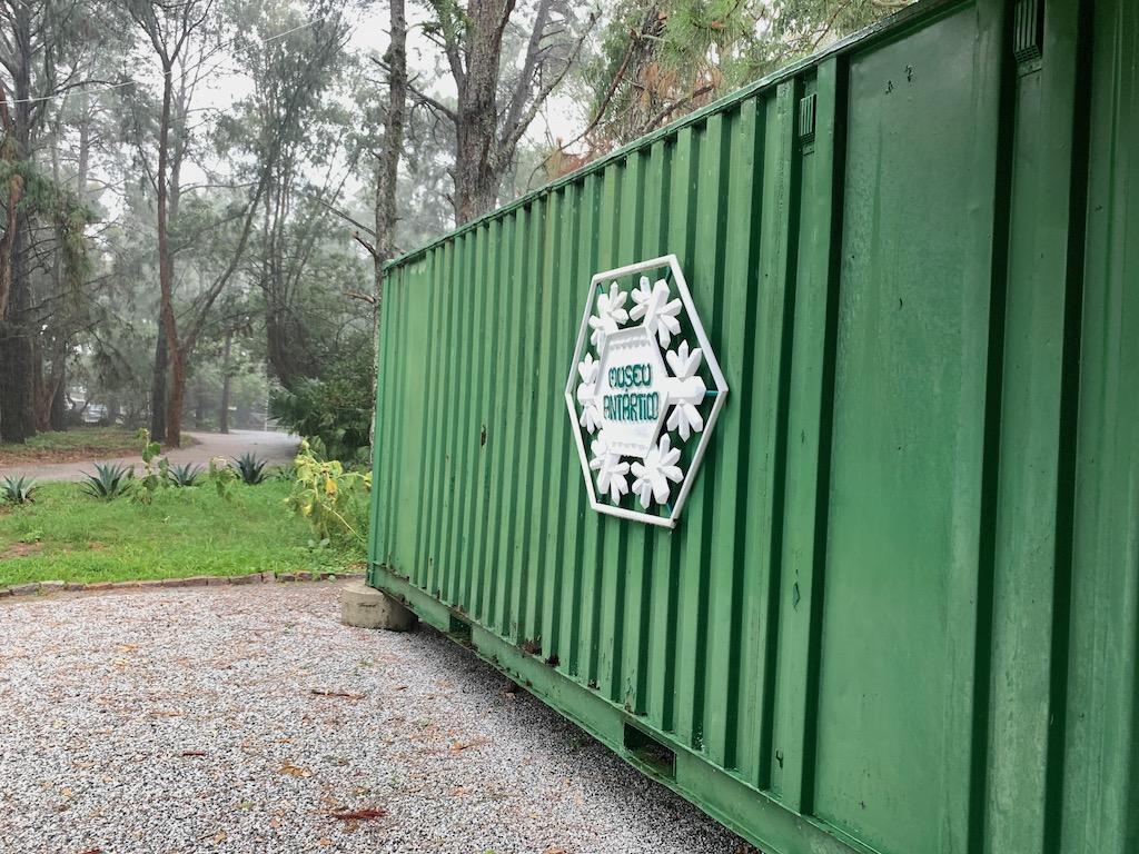 container verde com árvores ao fundo