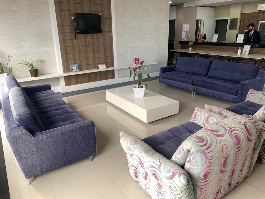 lobby de hotel com sofás, mesa, TV e recepção