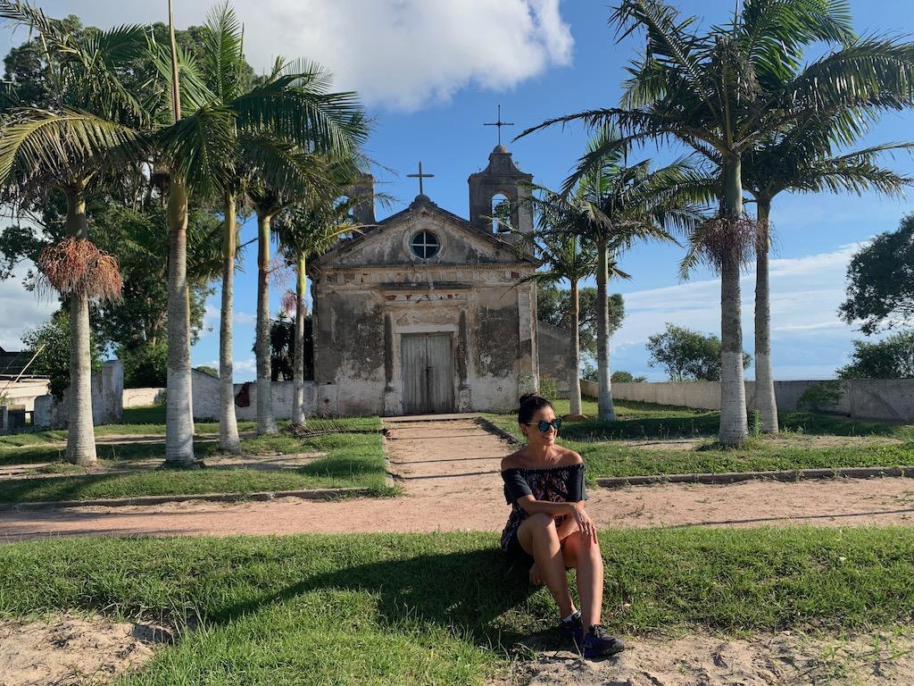 mulher sentada em frente à fachada da igreja capilha