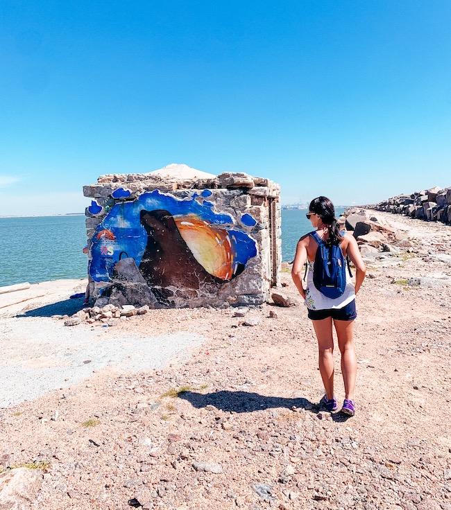 mulher caminhando em frente a casinha de pedra nos molhes