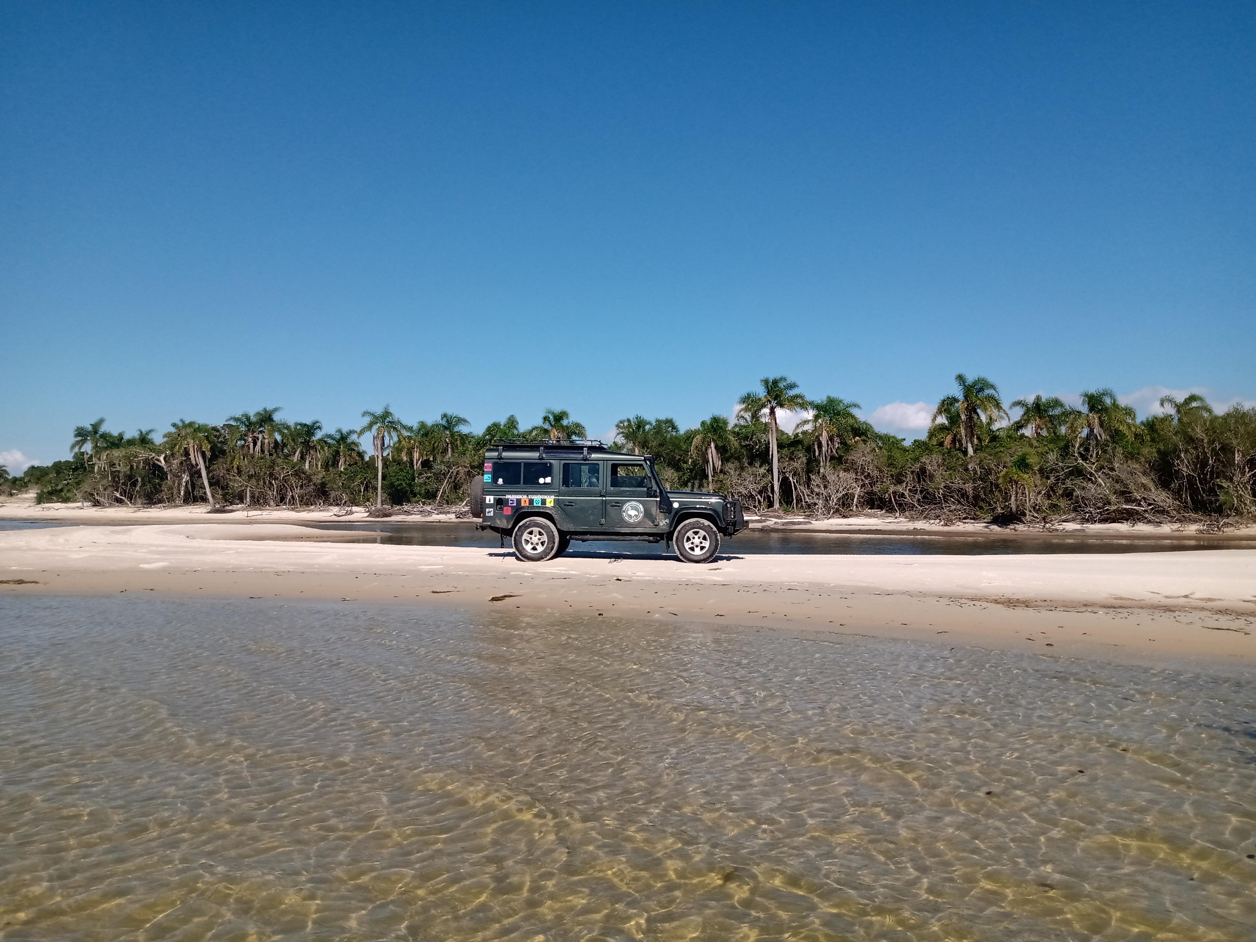 beira da lagoa com veículo na areia e coqueiros ao fundo