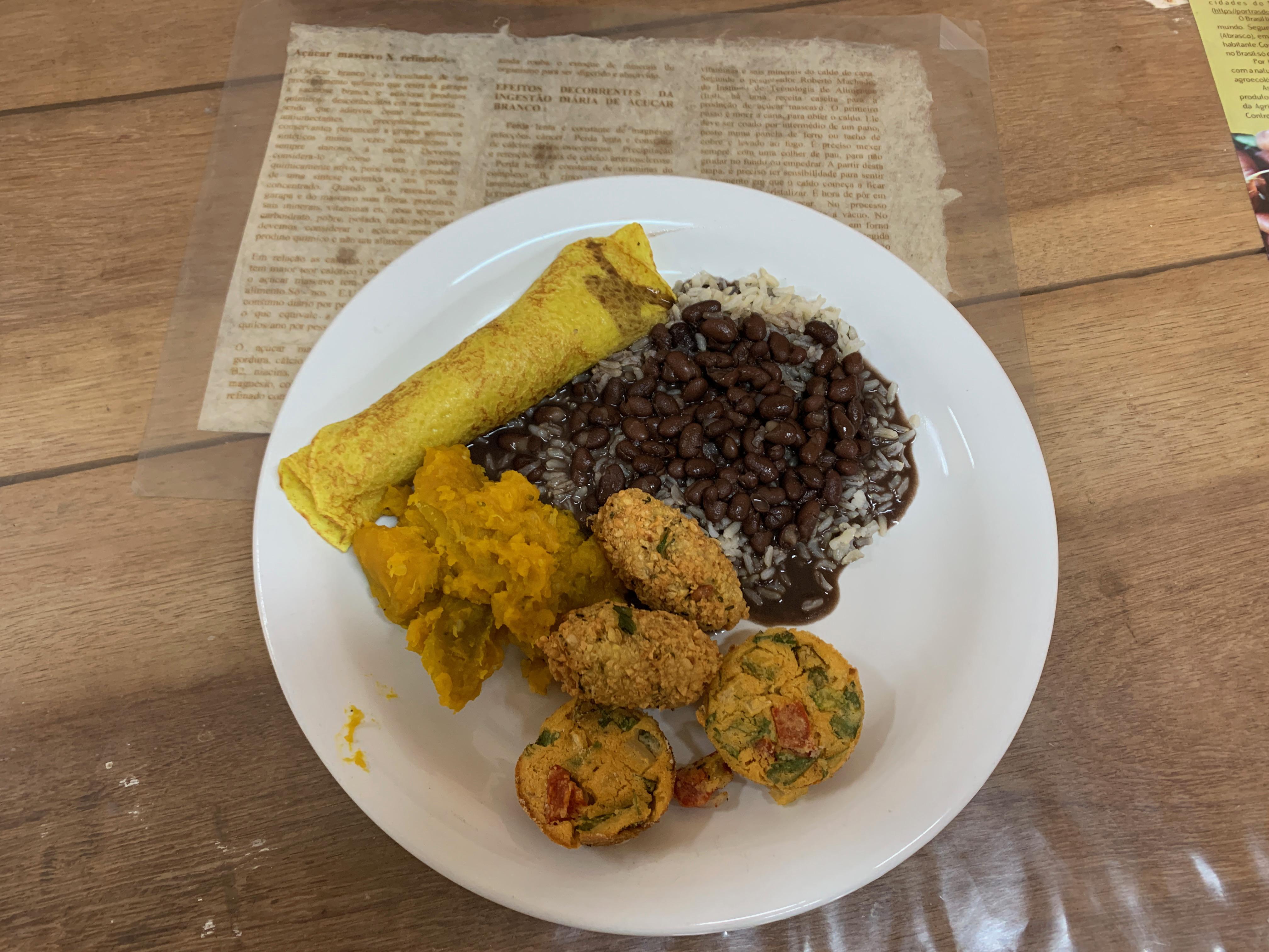 prato com arroz, feijão, panqueca de espinafre e berinjela com tomate