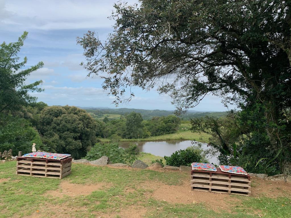 árvores, espaço para sentar com almofadas, céu azul e um lago ao fundo