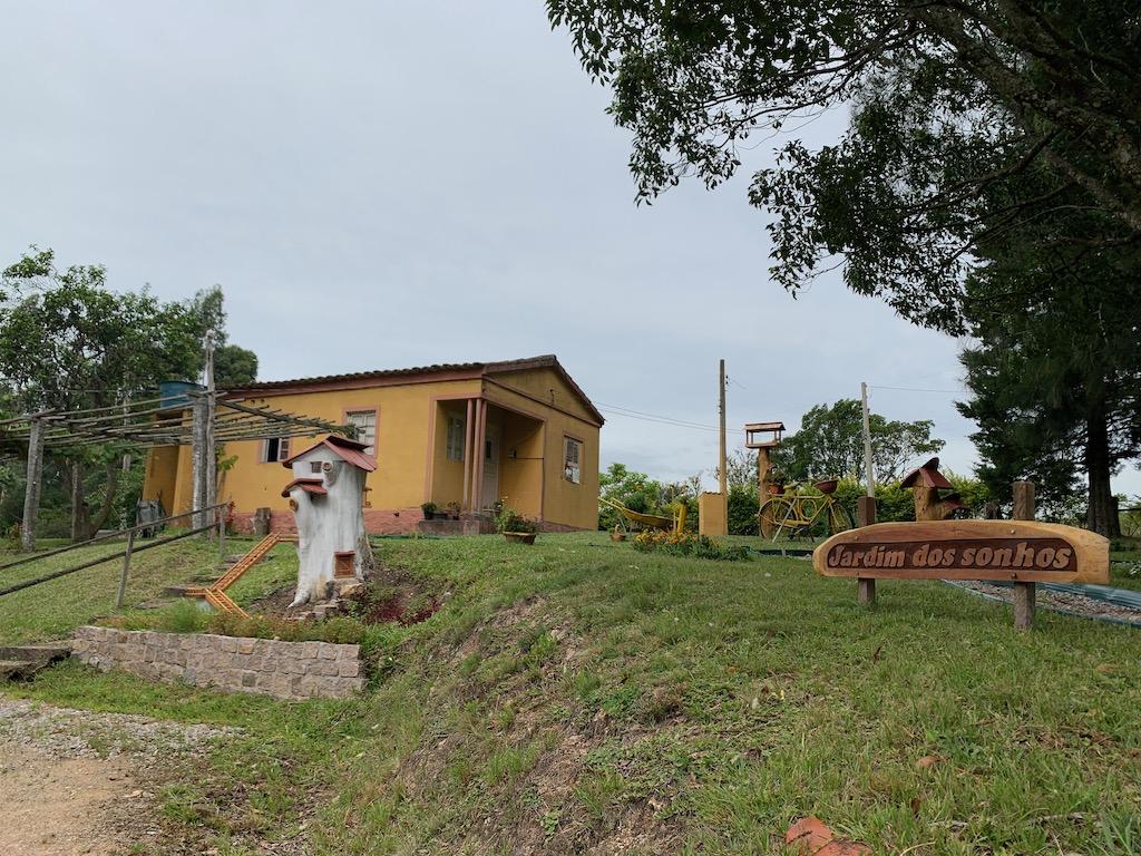 jardim com grama, uma casa ao fundo, árvore e uma casa esculpida em um tronco de árvore