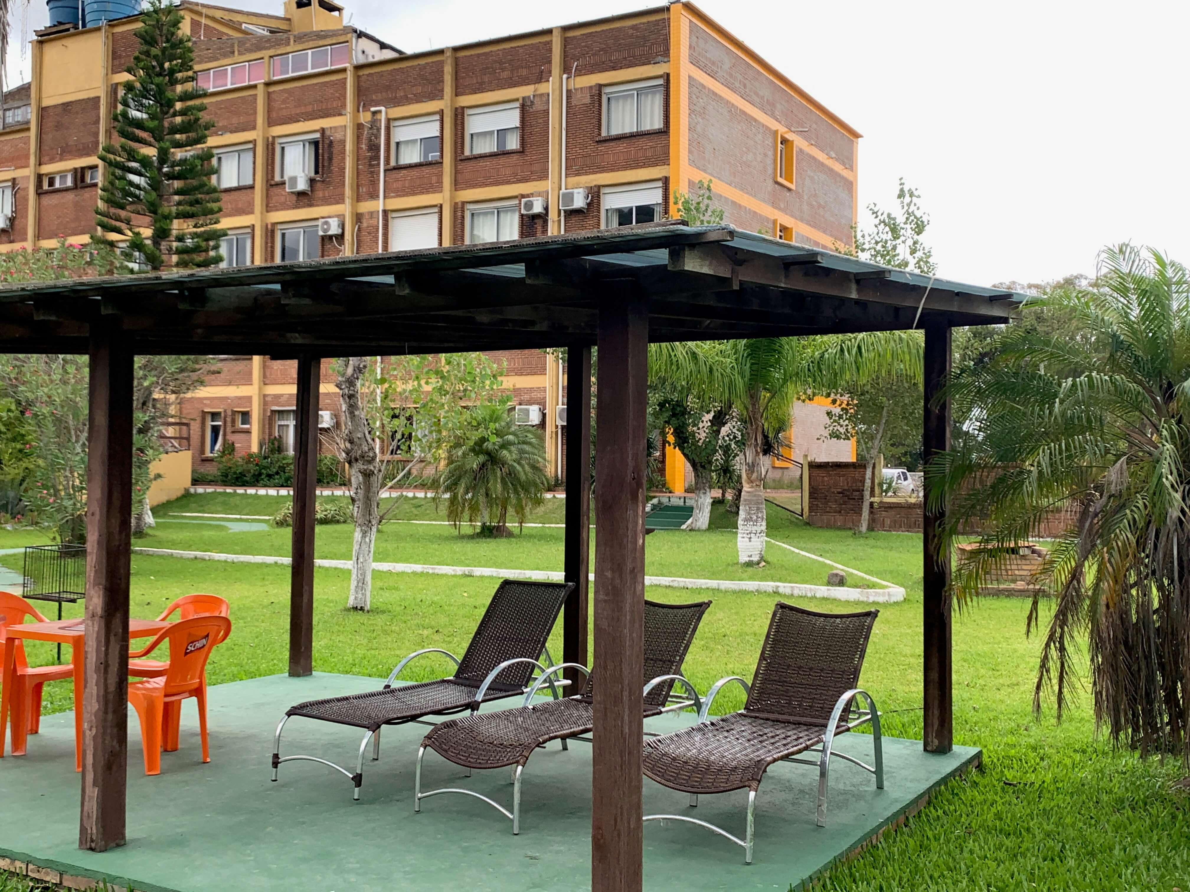 Parte externa do hotel Bertelli, com pergolado, cadeiras, árvores e área verde