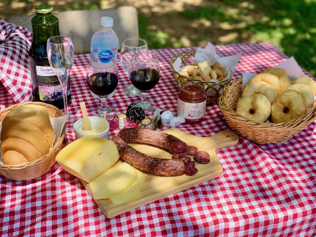 mesa de piquenique, com queijo, salame, pão, suco de uva, roda de carreta e geleias