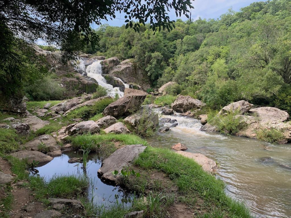 paisagem com cachoeira, pedras e árvores