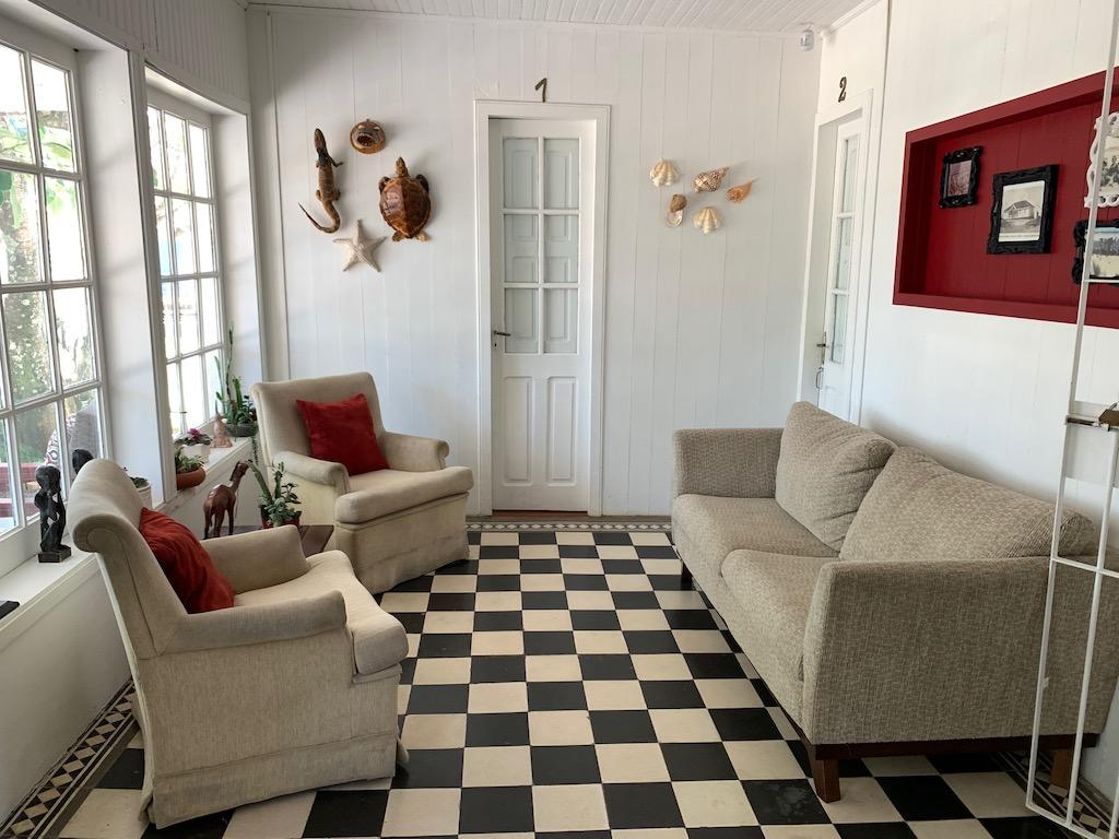 decoração da pousada Paraíso, com sofás, piso quadriculado e portas