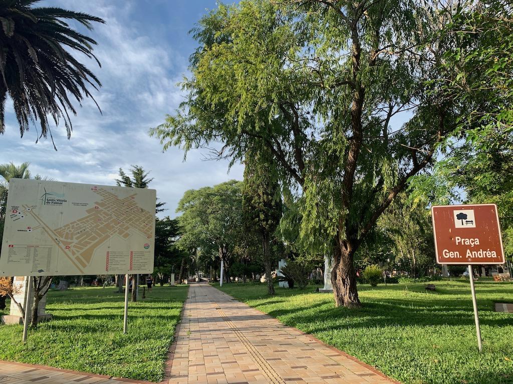 praça com árvores, grama, calçada e placas