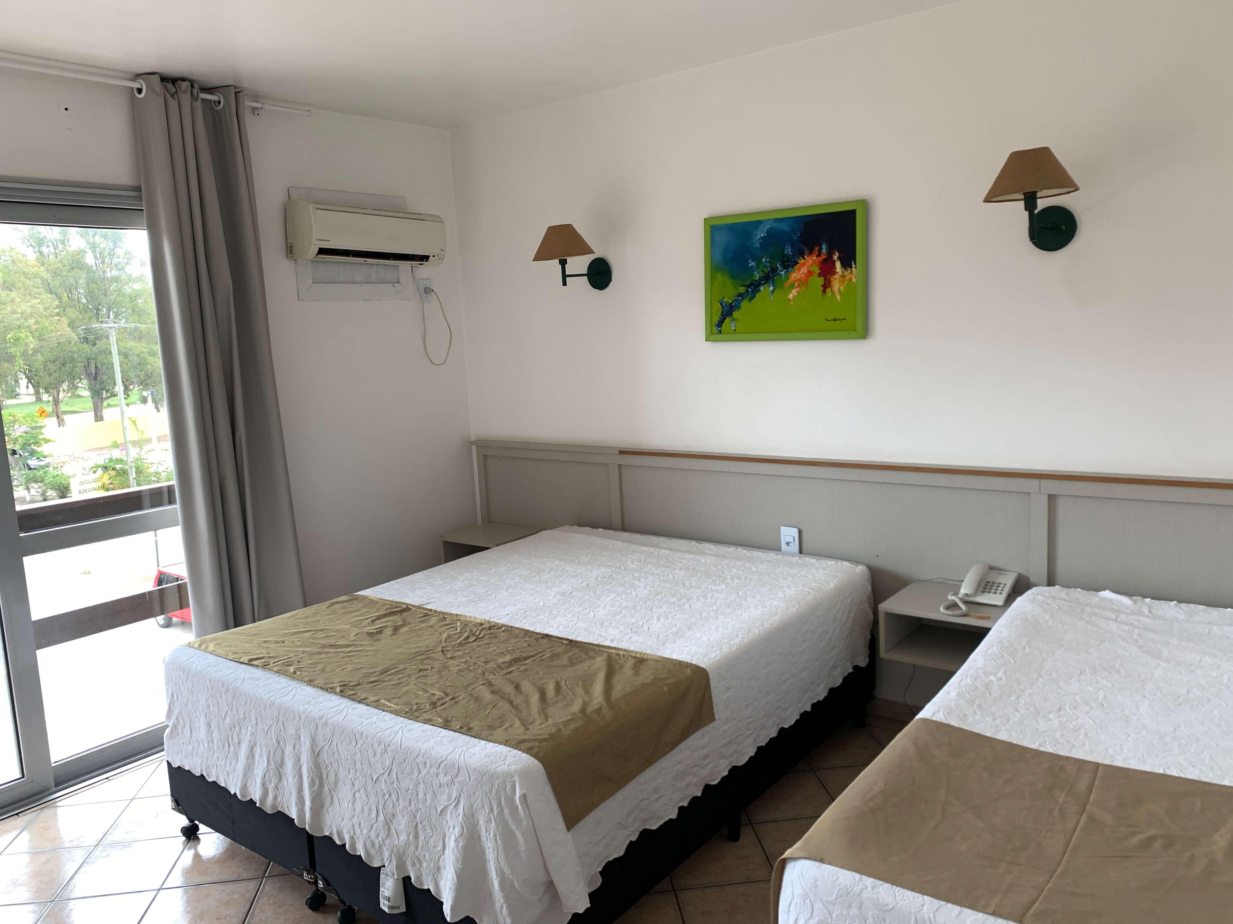 Quarto do hotel Bertelli, com duas camas, quadro, luminária e ar condicionado