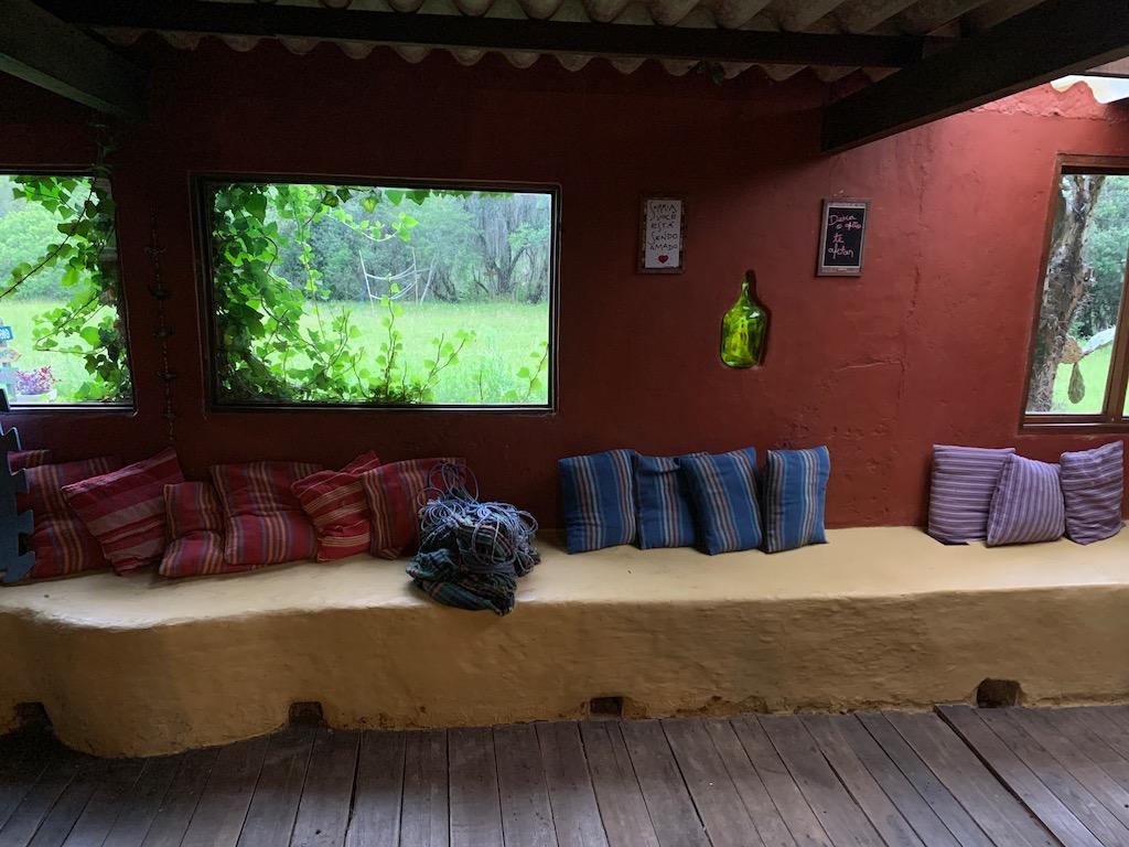 ambiente interno com almofadas e janelas com vista para o verde
