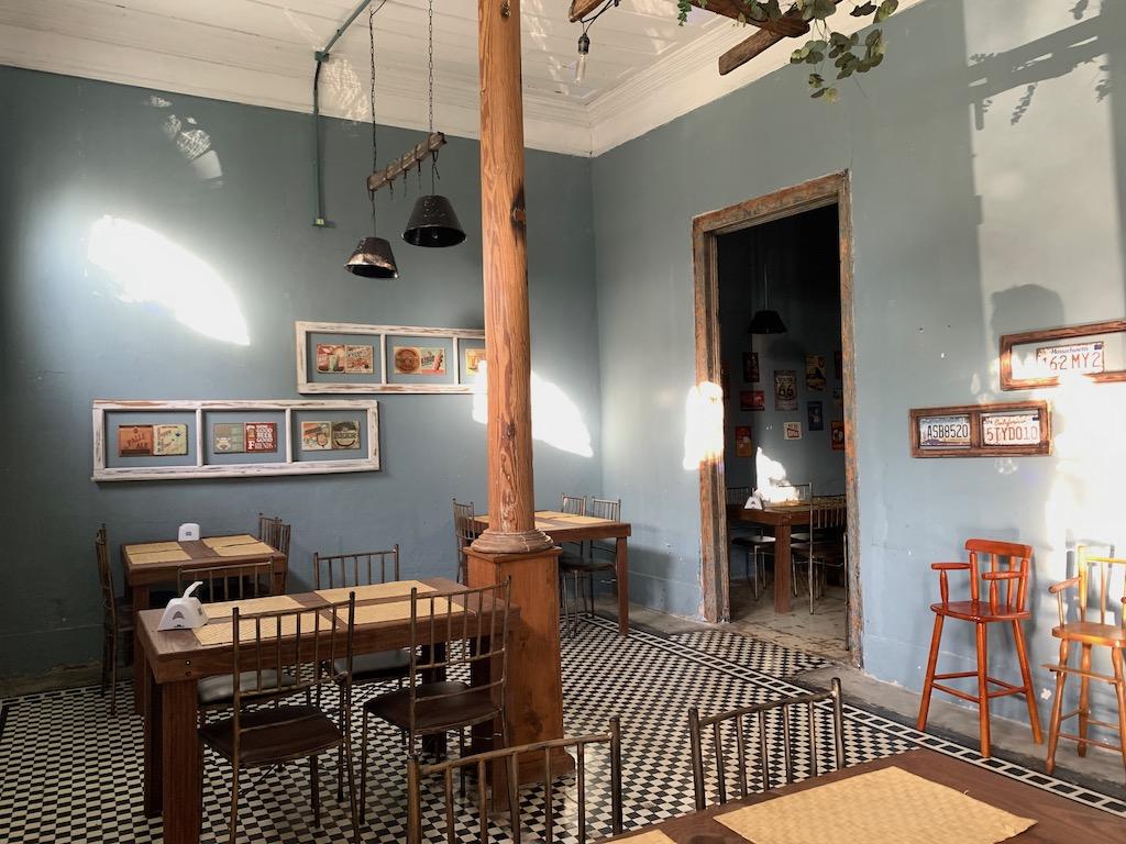 Foto interna do restaurante Cátia Clavijo, com mesas, cadeiras e quadros