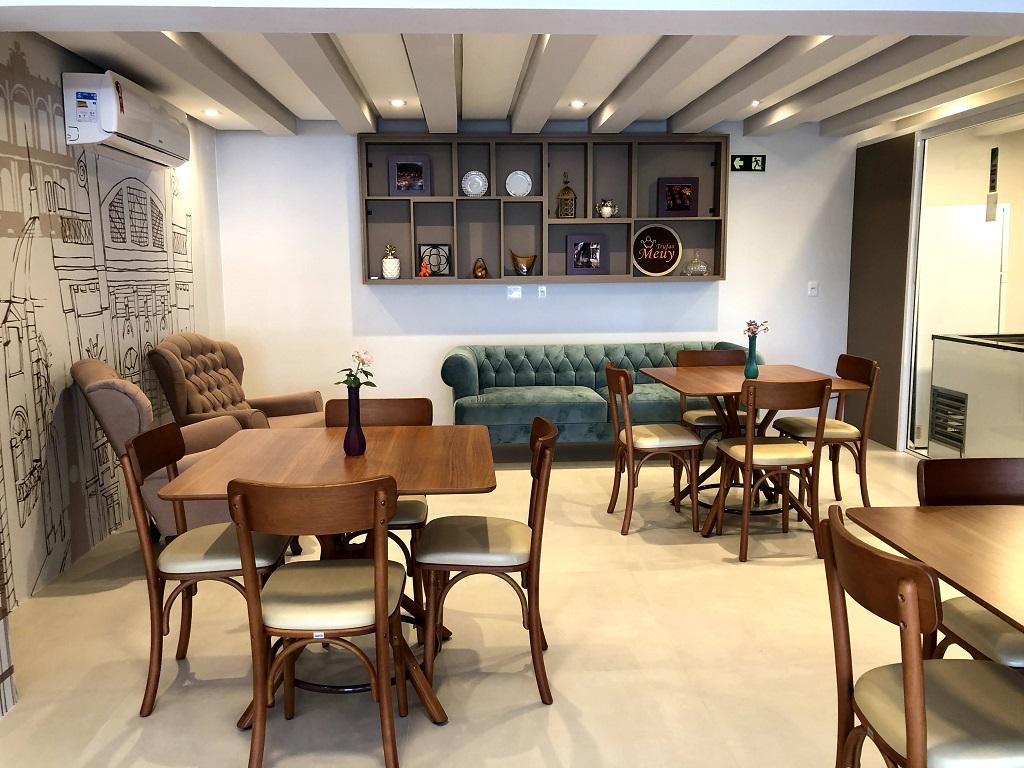 parte interna da loja de trufas, com cadeiras, mesas , sofá e parede com desenhos
