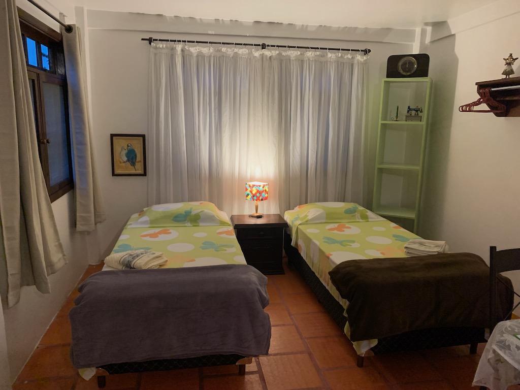 quarto com duas camas, cortina e mesinha