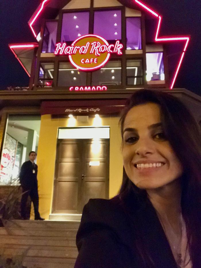fachada do Hard Rock Cafe à noite, com iluminação em vermelho e amarelo