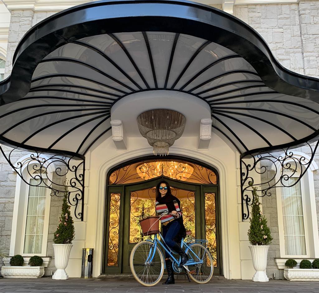 pessoa em uma bicicleta retrô na frente de um hotel