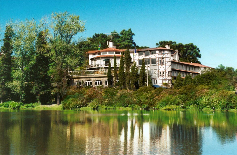 hotel localizado em frente a um lago, com árvores e céu azul