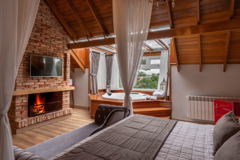 quarto de hotel, com lareira, hidromassagem, calefação e uma cama de casal