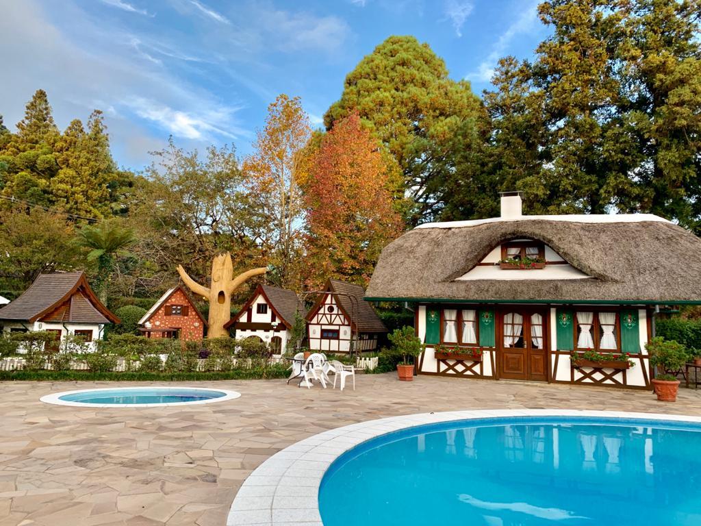 chalés, piscinas, cadeiras e árvores que formam a estrutura de um hotel