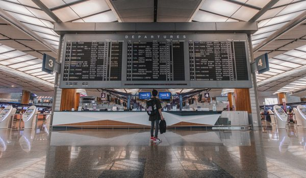 passageiro verifica voo no painel do aeroporto